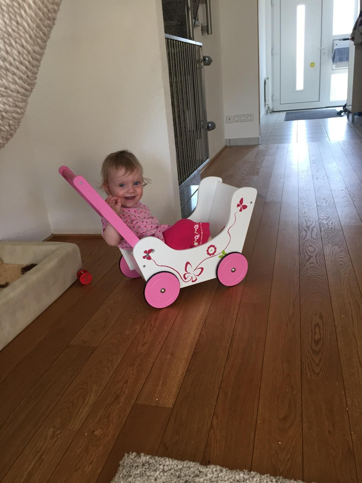Ina sitzt in ihrem Puppenwagen